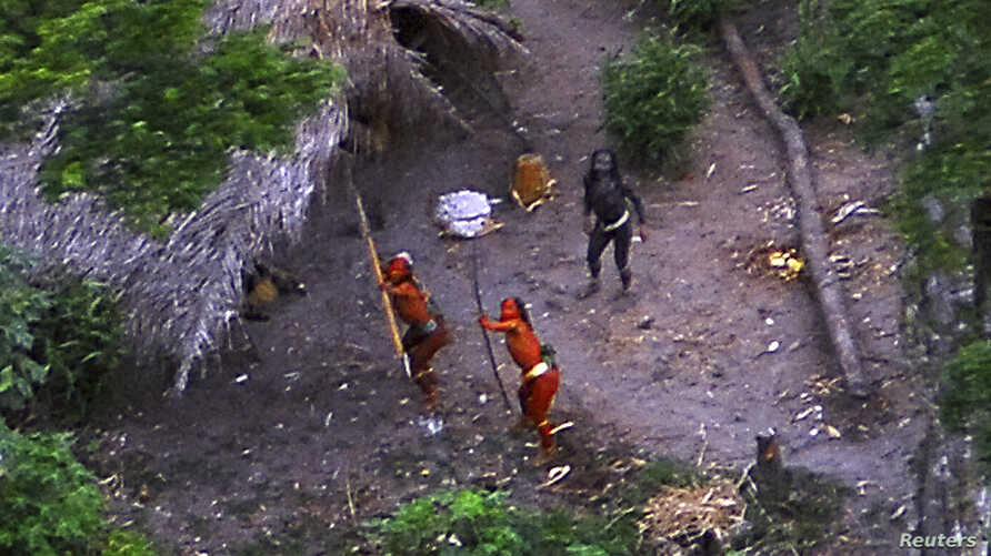 Members of an uncontacted Amazon Basin tribe and their dwellings are seen during a flight over the Brazilian state of Acre along the border with Peru in May, 2008.
