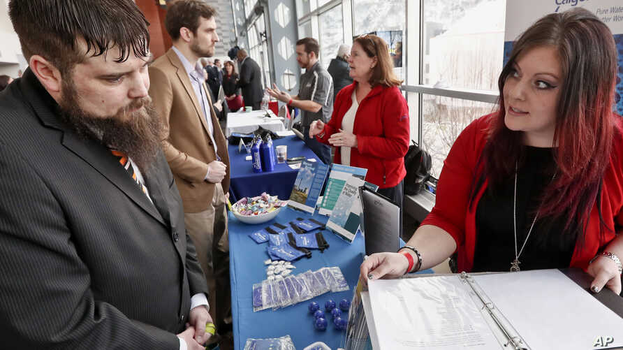 FILE - visitors to the Pittsburgh veterans job fair meet with recruiters at Heinz Field in Pittsburgh.