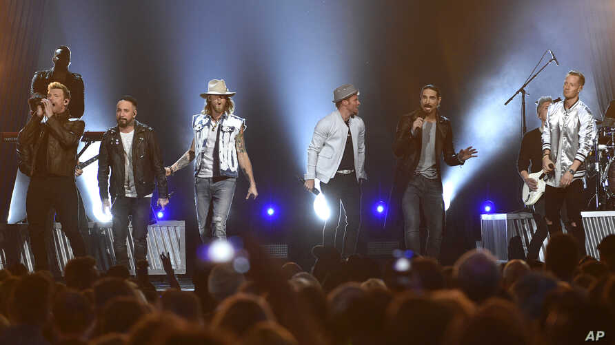 FILE - In this April 2, 2017, photo, Tyler Hubbard, from right, and Brian Kelley, third from left, of Florida Georgia Line, and from left, Nick Carter, AJ McLean, Brian Littrell, and Kevin Richardson, of Backstreet Boys, perform at the 52nd annual Ac