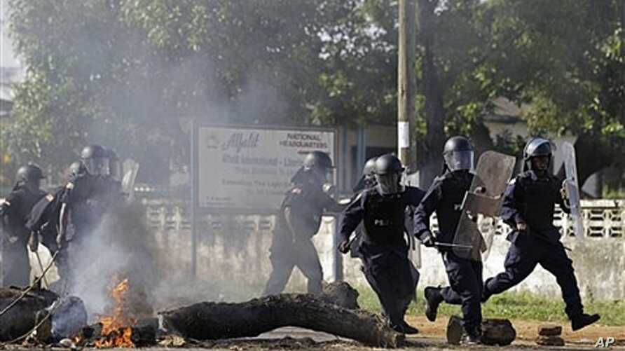 Liberian police advance past burning barricade as they chase opposition party supporters in Monrovia, Nov. 7, 2011.