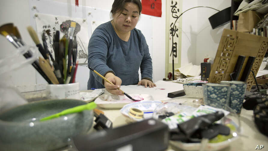 In this Feb. 27, 2017 photo, Ye Haiyan paints a watercolor painting in her studio on the outskirts of Beijing.