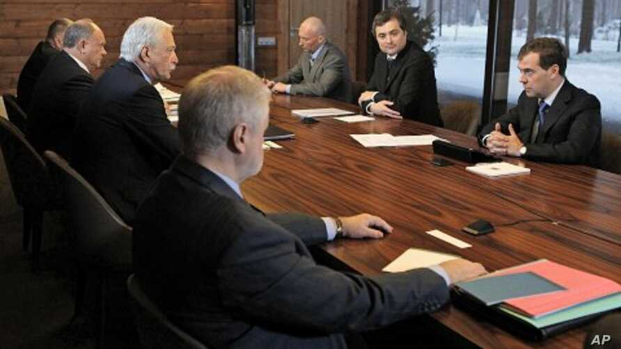 Russian President Dmitry Medvedev, right, speaks at his meeting with leaders of parties that won seats in the State Duma, in the Gorki residence outside Moscow, December 13, 2011.