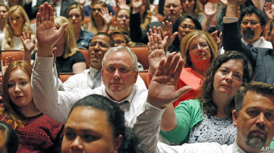 """Mormons participate in a long-standing custom called a """"sustaining"""" when Latter-day Saints stand and raise their hands during the twice-annual conference of the Church of Jesus Christ of Latter-day Saints, Oct. 6, 2018, in Salt Lake City."""