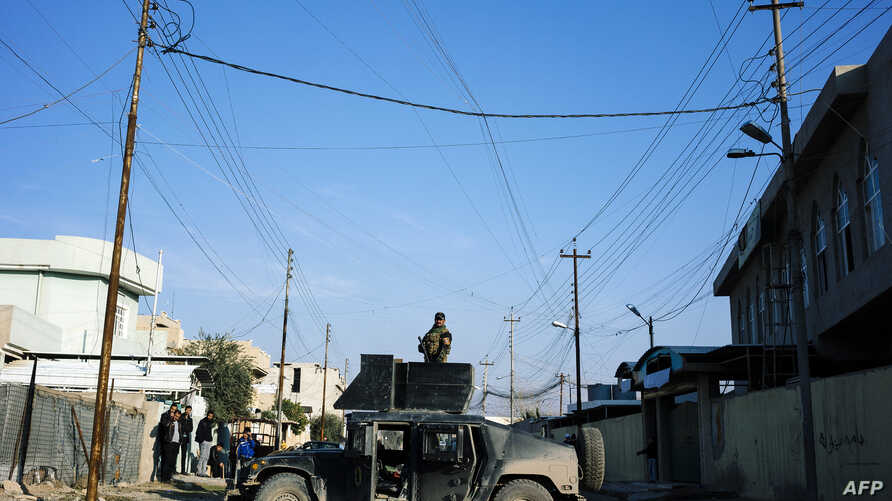 A member of the Iraqi special forces' Counter-Terrorism Service (CTS) stands on the top of a Humvee as demining experts search for booby-trapped buildings in eastern Mosul, Iraq, Jan. 16, 2017.