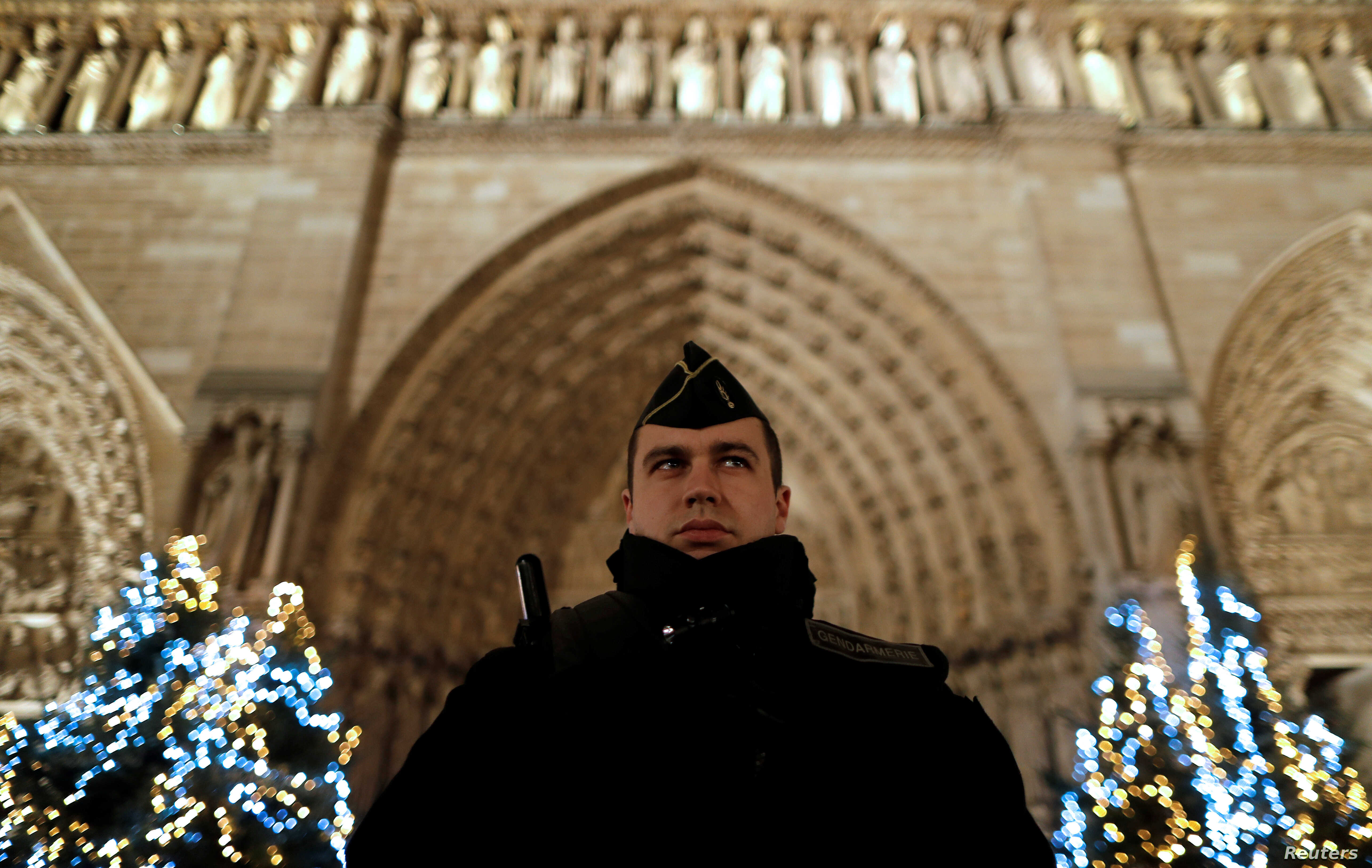 A French gendarme stands guard as heavy police forces secure the access to Notre-Dame cathedral during Christmas celebrations in Paris, France, Dec. 24, 2016.