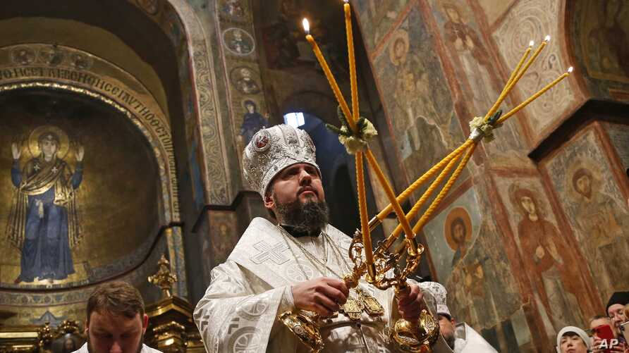 FILE - Metropolitan Epiphaniy, the head of the newly-formed independent Ukrainian Orthodox Church, conducts a service in St. Sophia Cathedral in Kyiv, Ukraine, Jan. 7, 2019.