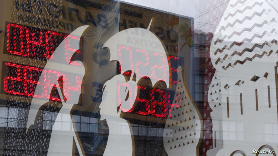 FILE - A board displaying currency exchange rates is reflected in a shop window in central Moscow, August 29, 2014.