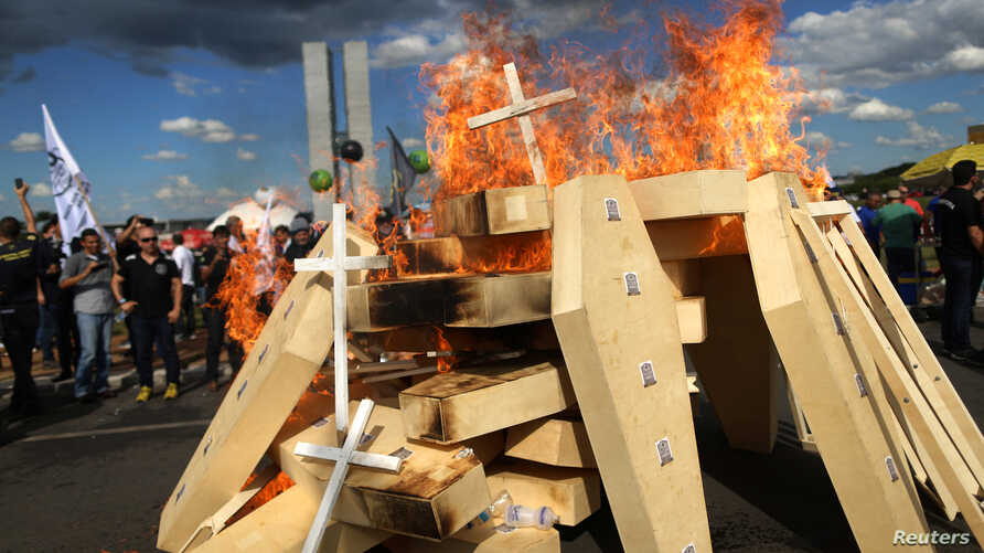 Striking police officers set fire to coffins during a protest by Police officers from several Brazilian states against pension reforms proposed by Brazil's president Michel Temer, in Brasilia, Brazil April 18, 2017.
