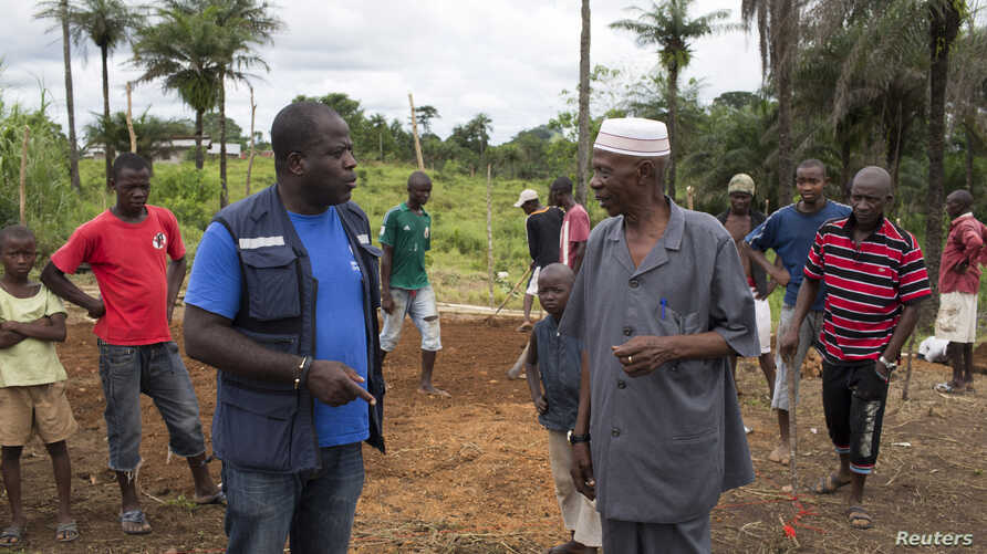 Kande-Bure Kamara from WHO speaks with community leaders at the construction site of a Ebola Care Unit in Kamasondo Village, Port Loko District, Oct. 8, 2014.