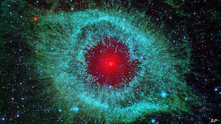 This infrared image from NASA's Spitzer Space Telescope shows the Helix nebula, with a white dwarf visible as a tiny white dot in the center of the picture.