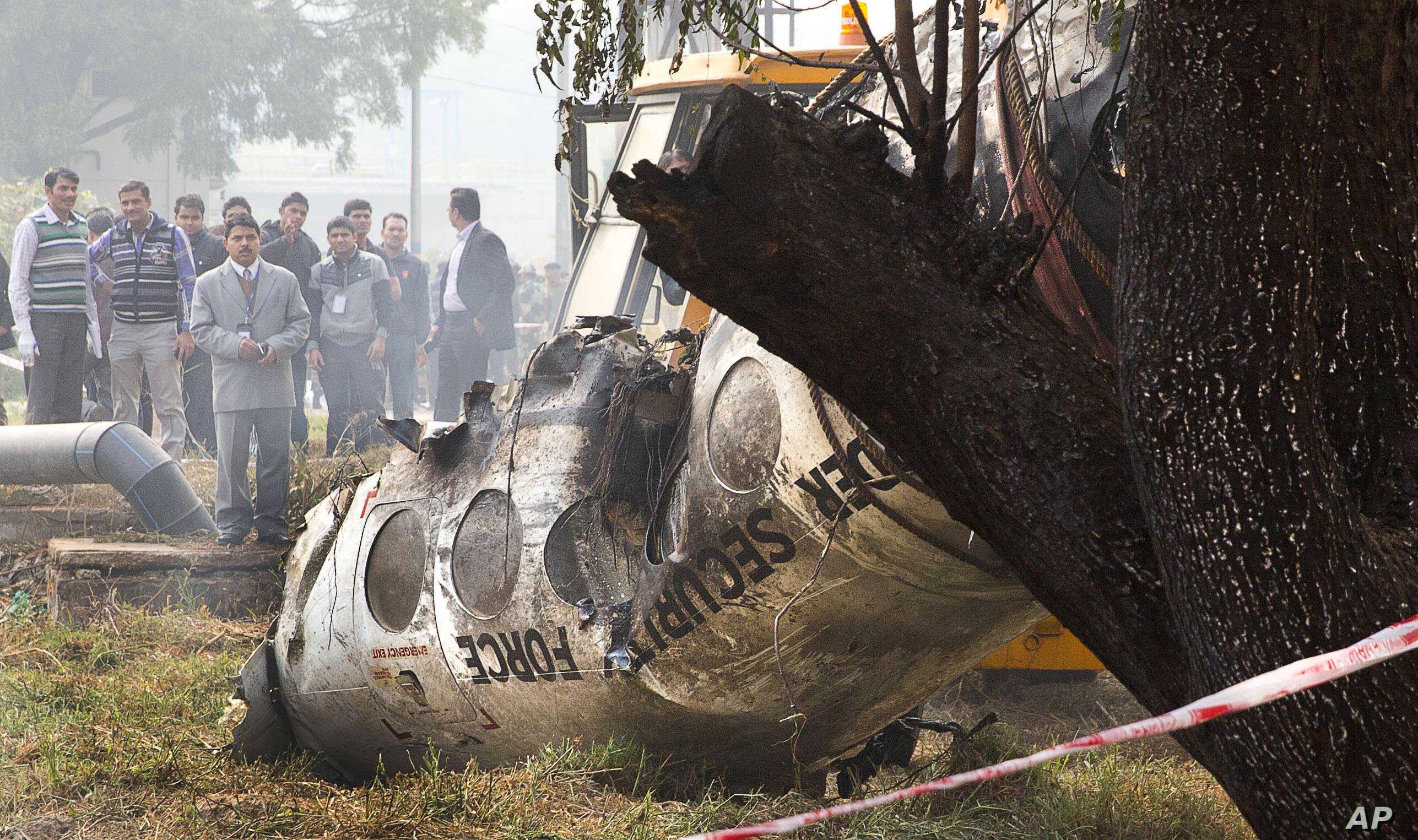 Investigators look at the remains of a small Indian paramilitary plane that crashed outside the airport in New Delhi, India, Dec. 22, 2015.
