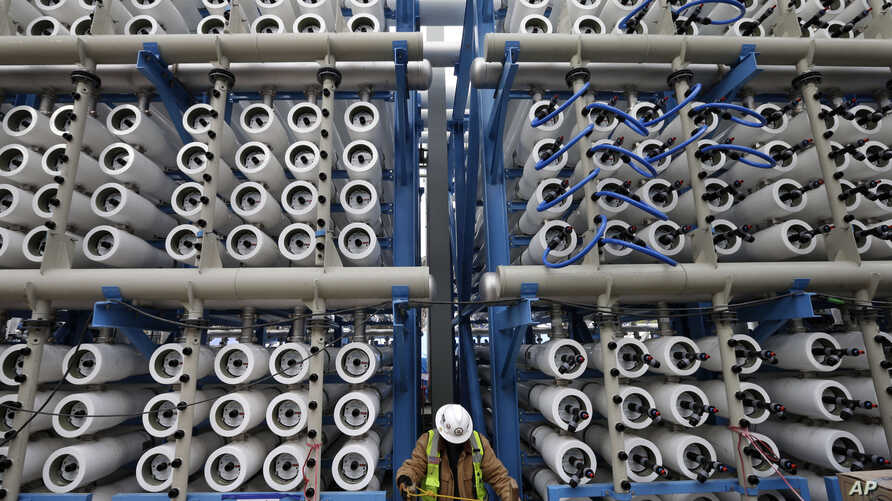 FILE - A worker climbs stairs among some of the 2,000 pressure vessels that will be used to convert seawater into fresh water through reverse osmosis in a desalination plant in Carlsbad, Calif., March 11, 2015.