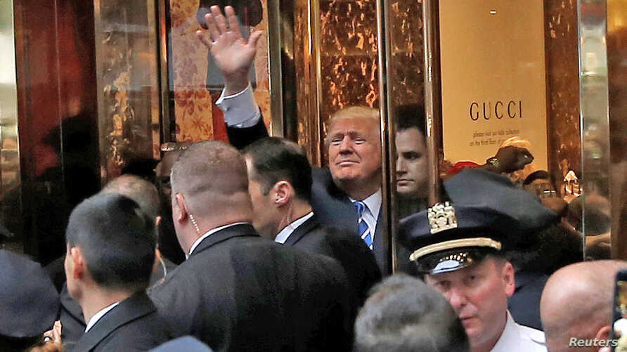 Republican presidential nominee Donald Trump waves to supporters outside the front door of Trump Tower where he lives in the Manhattan borough of New York, Oct. 8, 2016.