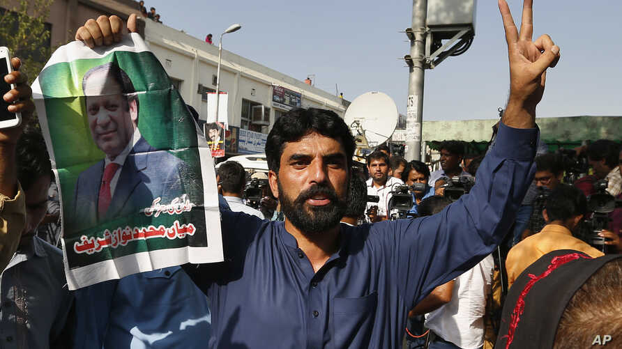 A supporter of former Pakistani Prime Minister Nawaz Sharif holds his picture and makes a victory sign after a court ruling, outside the Islamabad High Court in Islamabad, Pakistan, Sept. 19, 2018.