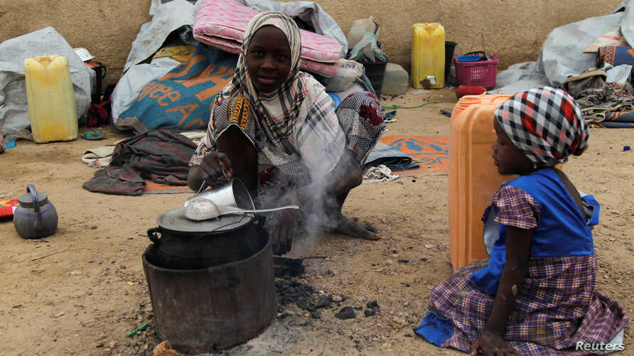 A displaced girl cooks at an arena for traditional wrestling in the town of Diffa in southeastern Niger June 20, 2016.