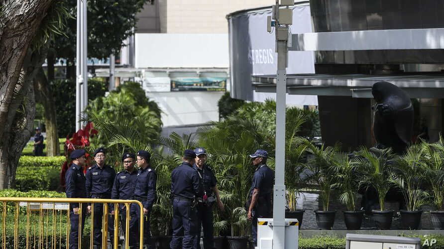 Police officers patrol the perimeter of the St. Regis Hotel in Singapore, June 11, 2018, ahead of the summit between U.S. President Donald Trump and North Korean leader Kim Jong Un.