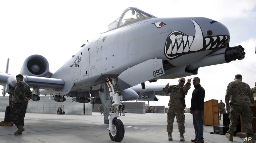 FILE - U.S. military forces stand beside an A-10C Thunderbolt II ground attack aircraft at Kandahar Airfield, Afghanistan, Jan. 23, 2018.