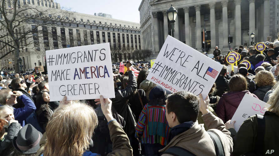 People hold anti-deportation signs during a rally, March 9, 2017, in New York. The rally was held in support of Ravi Ragbir, leader of the New Sanctuary Coalition, and an immigrant from Trinidad, who may face deportation.