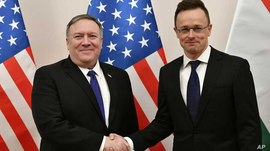 Hungarian Minister of Foreign Affairs and Trade Peter Szijjarto, right, shakes hands with US Secretary of State Mike Pompeo in the ministry in Budapest, Hungary, Feb. 11, 2019.