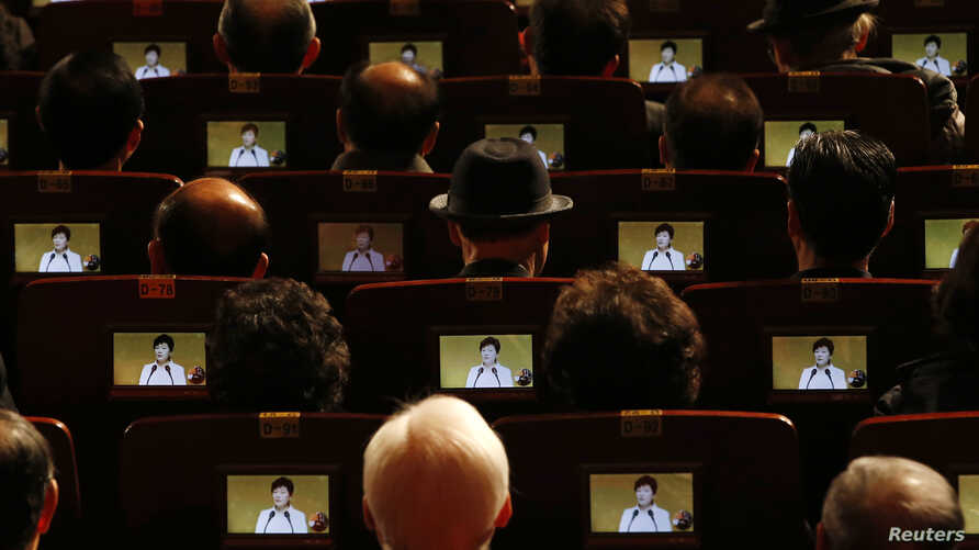 People watch South Korean President Park Geun-hye's speech on small screens fitted in their seats during a ceremony celebrating the 96th anniversary of the Independence Movement Day in Seoul March 1, 2015. This year commemorates the 96th year of the