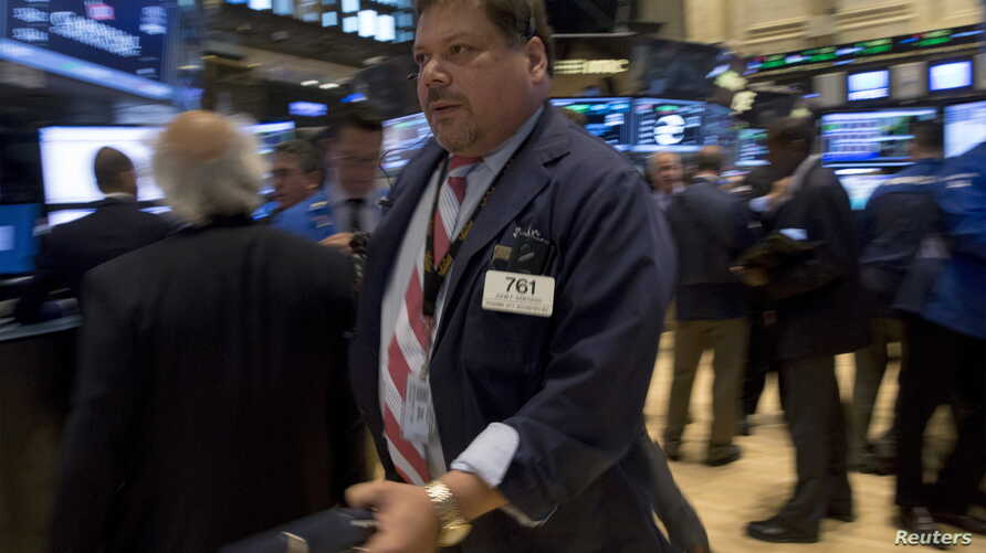 Traders work on the floor of the New York Stock Exchange July 14, 2015.