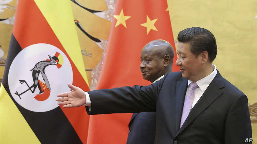 FILE - Ugandan President Yoweri Museveni, left, is shown the way by Chinese President Xi Jinping as they attend a signing ceremony in the Great Hall of the People in Beijing, China, March 31, 2015.