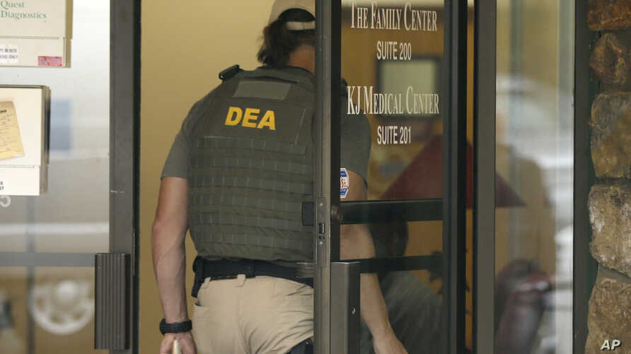 FILE A Drug Enforcement Administration officer walks into a medical clinic in Little Rock, Ark., Wednesday, May 20, 2015.