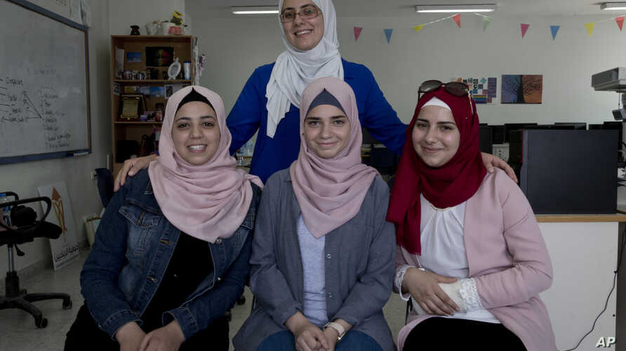 Tamara Awaysa, 17, left, Wassan al-Sayyed,17, center and Massa Halawa,16, right, pose for a photo with their mentor Yamama Shakaa in the West Bank city of Nablus. For the 11th graders from the Israeli-occupied West Bank, the ticket of admission to th