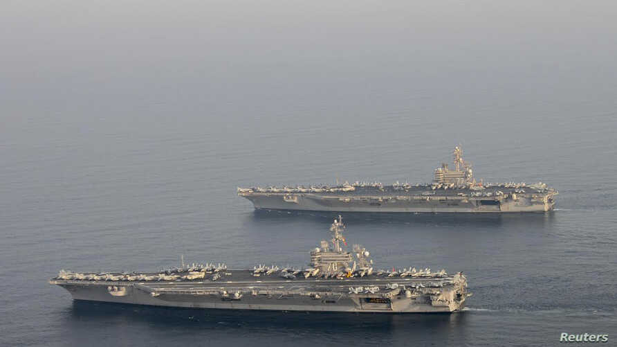 FILE - The U.S. Navy aircraft carrier USS Carl Vinson (CVN 70), bottom, is seen relieving the USS George H.W. Bush in the Arabian Gulf, Oct. 18, 2014.