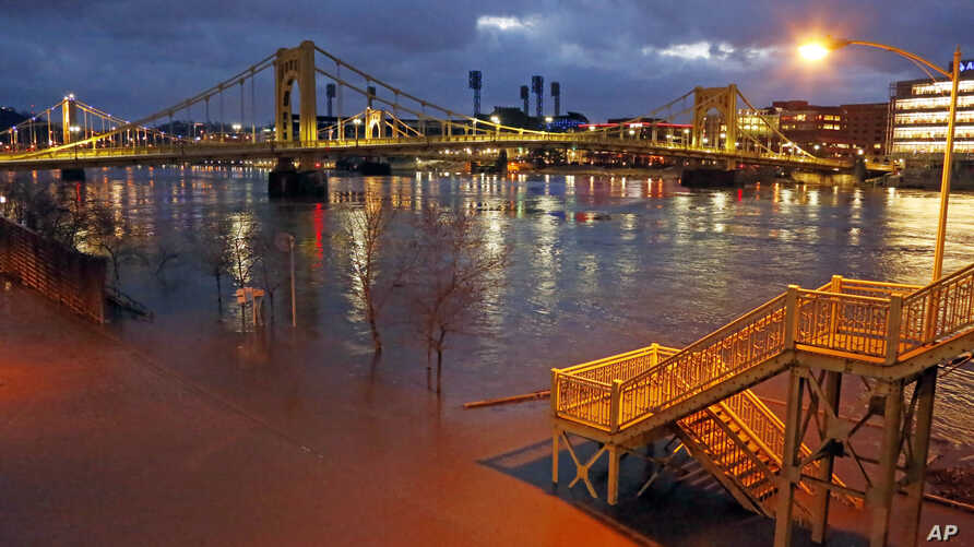 Steps to the Ninth Street bridge and Duquesne Boulevard in downtown Pittsburgh are flooded as the Allegheny River overflows its banks Feb. 16, 2018. A band of thunderstorms is bringing more rain into parts of the country already under high water.