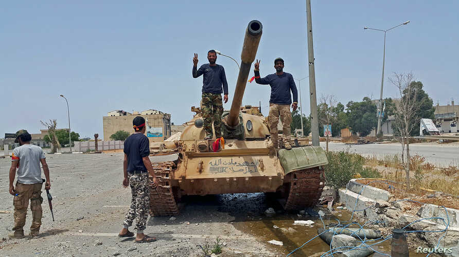 Members of Libya's pro-government forces gesture as they stand on a tank in Benghazi, Libya, May 21, 2015.