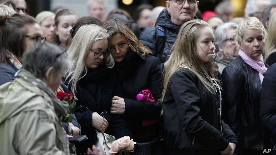 People observe a minute of silence near the department store Ahlens in Stockholm, Sweden, April 10, 2017, to honor the four killed victims and 15 injured in a fatal truck attack. T