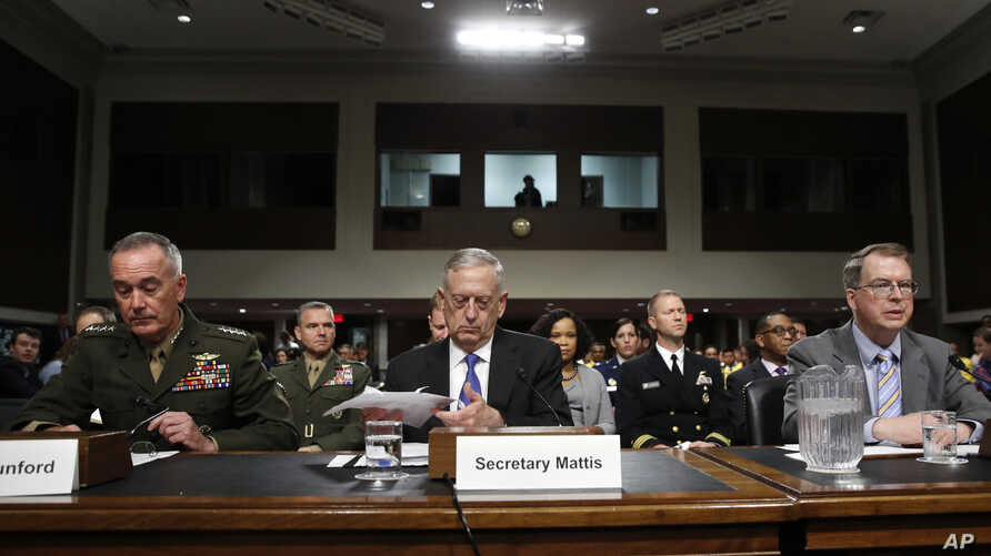 Defense Secretary Jim Mattis, center, flanked by Joint Chiefs Chairman Gen. Joseph Dunford, left, and Defense Undersecretary David Norquist, prepares to testify on Capitol Hill in Washington, June 13, 2017, before a Senate Armed Services Committee he