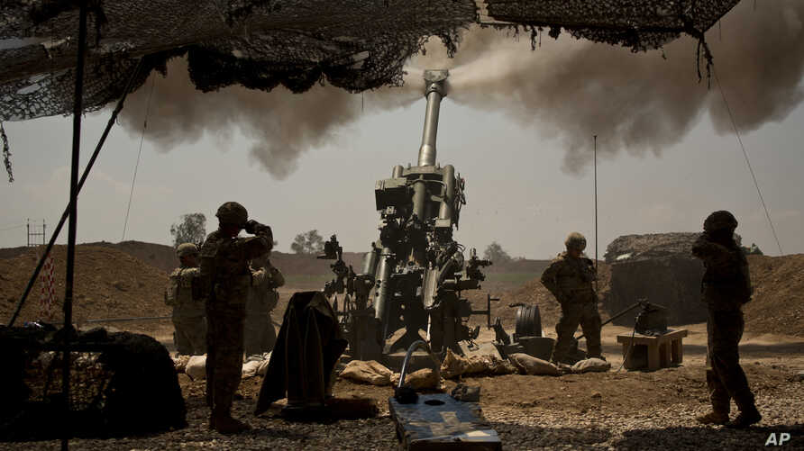 U.S. soldiers from the 82nd Airborne Division fire artillery in support of Iraqi forces fighting Islamic State militants from their base east of Mosul on Monday, April 17, 2017.