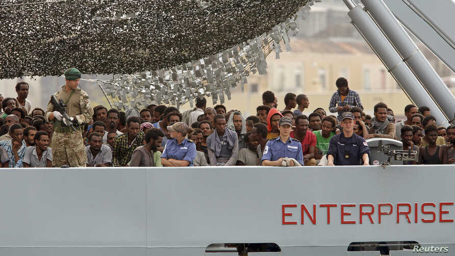 Migrants arrive on the British vessel HMS Enterprise before disembarking in the Sicilian harbor of Catania, Italy, Oct. 6, 2015.