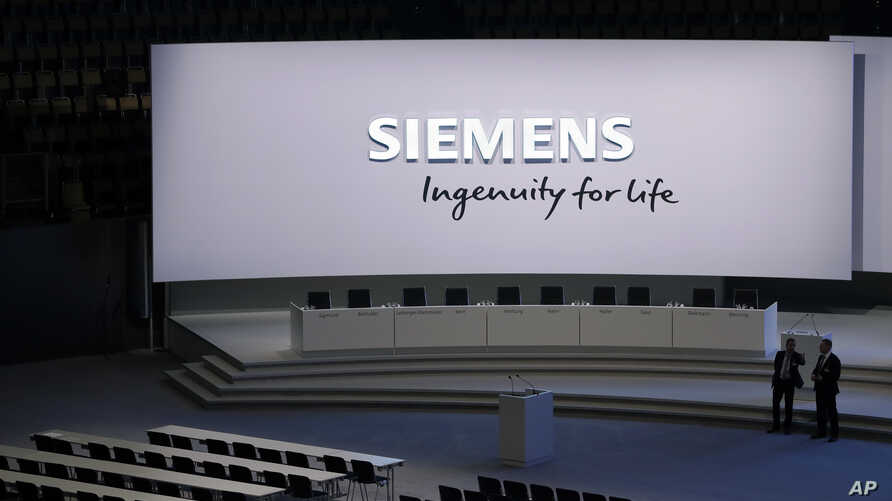 Security stewards of German industrial conglomerate Siemens wait for the start of the annual shareholders meeting in Munich, Germany, Feb. 1, 2017.