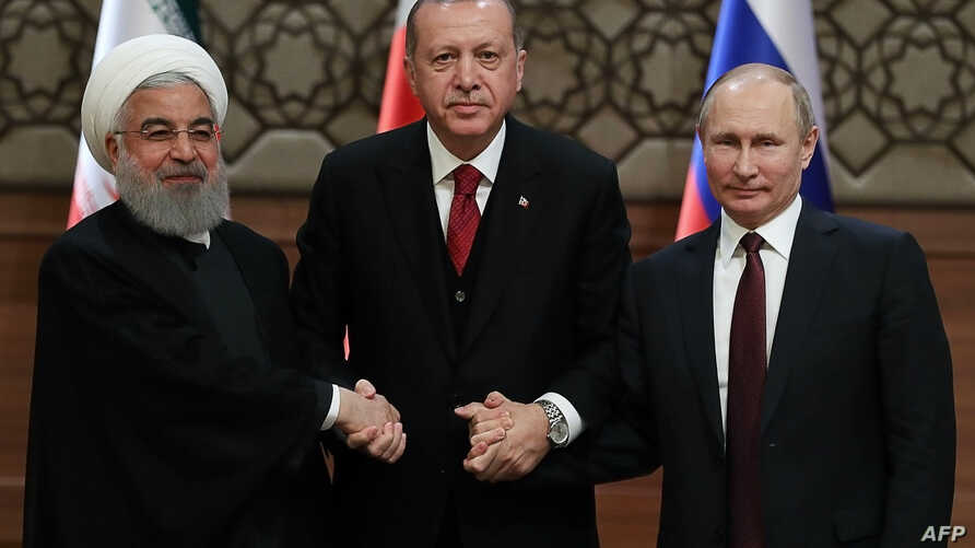 FILE - Iran's President Hassan Rouhani, from left, Turkey's President Recep Tayyip Erdogan  and Russia's President Vladimir Putin shake hands after a joint press conference as part of a tripartite summit on Syria, in Ankara, April 4, 2018.