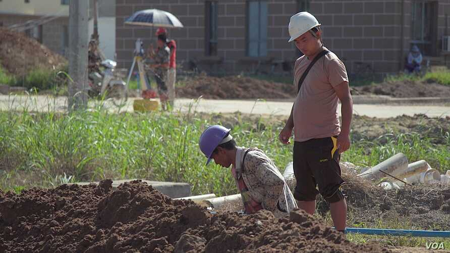 A Chinese engineer watches over a Burmese laborer at the construction site of the Chinese resort project, near Shwe Koko, Karen state, Myanmar.