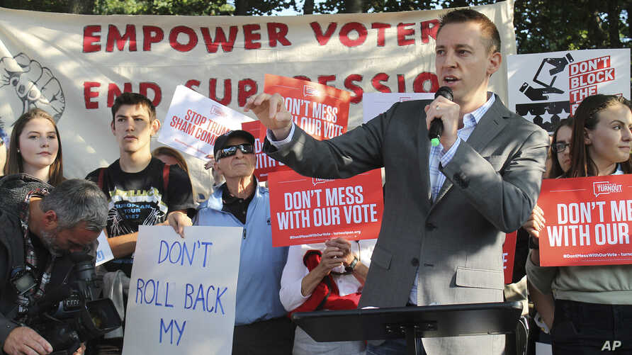 """The founder of """"Let America Vote"""" speaks to protesters gathered outside Saint Anselm College in Manchester, N.H., where the Trump administration's commission on voter fraud met on Sept. 12, 2017."""