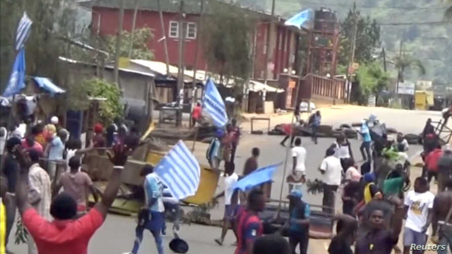 A still image taken from a video shot on October 1, 2017, shows protesters waving Ambazonian flags in front of road block in the English-speaking city of Bamenda, Cameroon.