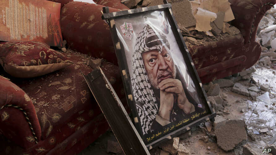 A poster of later Palestinian leader Yasser Arafat is seen on the rubble of a destroyed house in the Bureij refugee camp in the central Gaza Strip, Aug. 1, 2014.