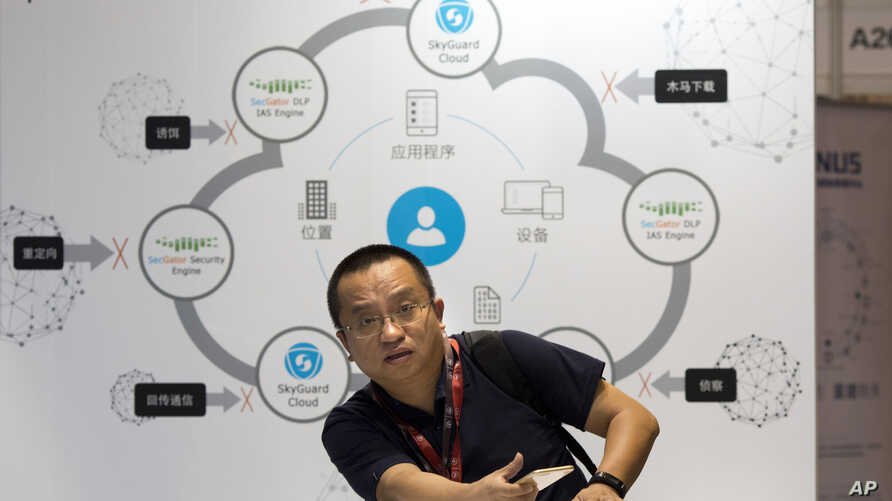 An attendee sits near a diagram illustrating cloud security during the 4th China Internet Security Conference (ISC) in Beijing, Aug. 16, 2016.