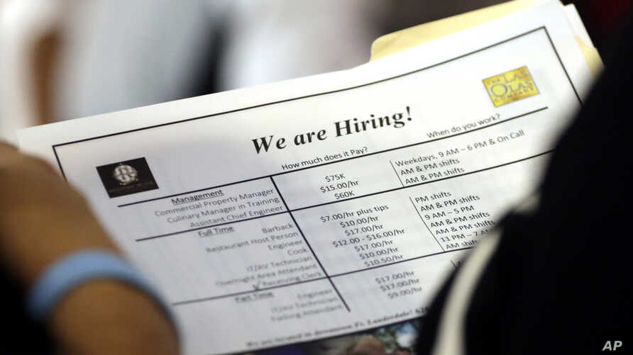 FILE - A job applicant looks at job listings for the Riverside Hotel at a job fair hosted by Job News South Florida, in Sunrise, Fla.