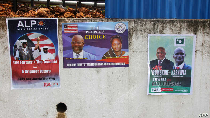 Picture taken July 31, 2017 in Monrovia shows campaign posters on a wall as the campaign kicks off for the presidency and House of Representatives elections in October.