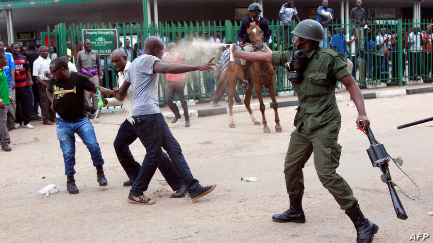 A police officer fires pepper spray at supporters of the opposition United Party for National Development outside the Woodlands Police Station in Lusaka, March 2, 2016.