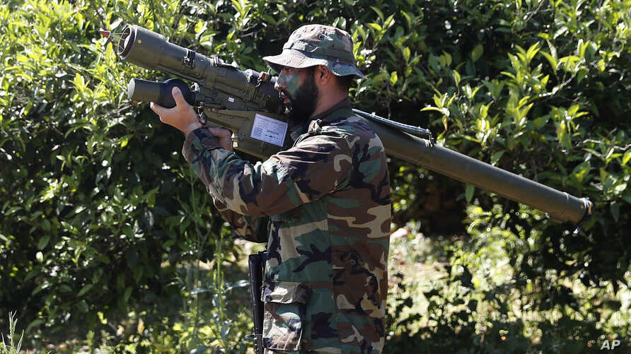FILE - A Hezbollah fighter holds an Iranian-made anti-aircraft missile on the border with Israel, in Naqoura, south Lebanon, April 20, 2017. The British government will make inciting support for Hezbollah a criminal offense.