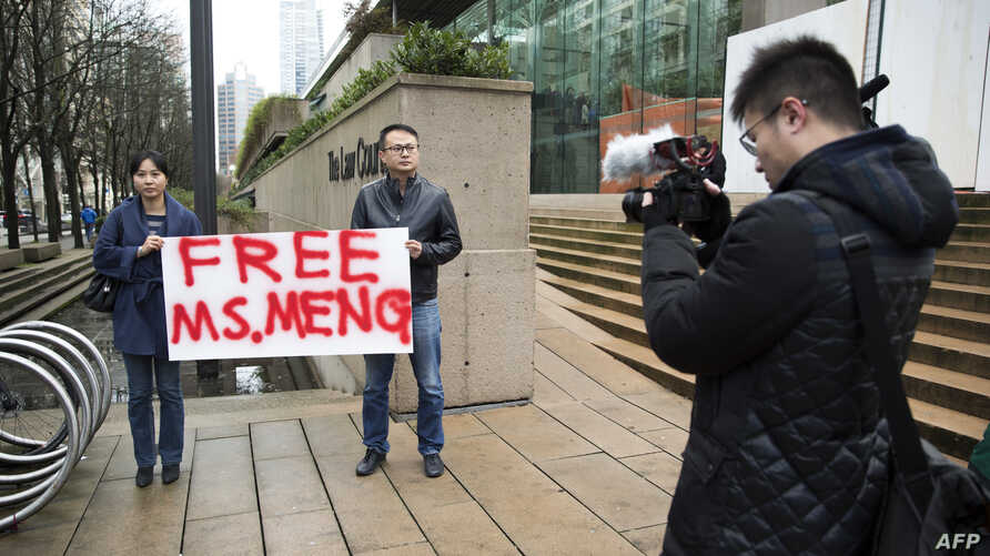 Ada Yu of Vancouver and a man who wished to remain unidentified, hold a sign in favor of the release of Huawei Technologies CFO Meng Wanzhou outside her bail hearing at British Columbia Superior Courts following her Dec. 1 arrest in Canada for extrad
