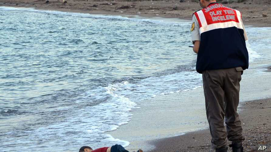FILE - In this Sept. 2, 2015 photo, a paramilitary police officer investigates the scene before carrying the lifeless body of 3-year-old Aylan Kurdi from the sea shore, near the beach resort of Bodrum, Turkey.