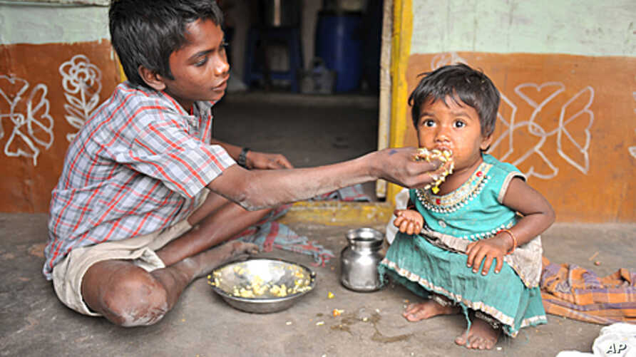 "An Indian boy feeds his sister at their home in a slum in Hyderabad.  Levels of under-nutrition in the country were ""unacceptably high"" despite impressive GDP growth, Prime Minister Manmohan Singh said Tuesday and added that the problem of malnutriti"