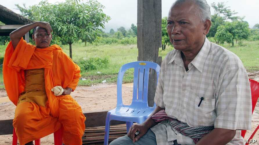FILE - Former Khmer Rouge navy commander Meas Muth, right, sits next to a Buddhist monk at Anlong Veng district in Oddar Mean Chey province, Cambodia, July 23, 2006. Meas Muth was implicated in the 1975 Mayaguez incident in which at least 38 U.S. ser
